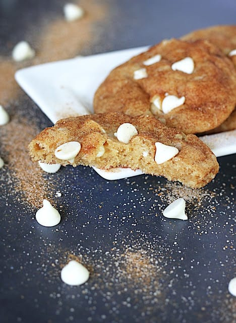 brown butter white chocolate chip snickerdoodles on white tray with a bite missing from the first cookie.
