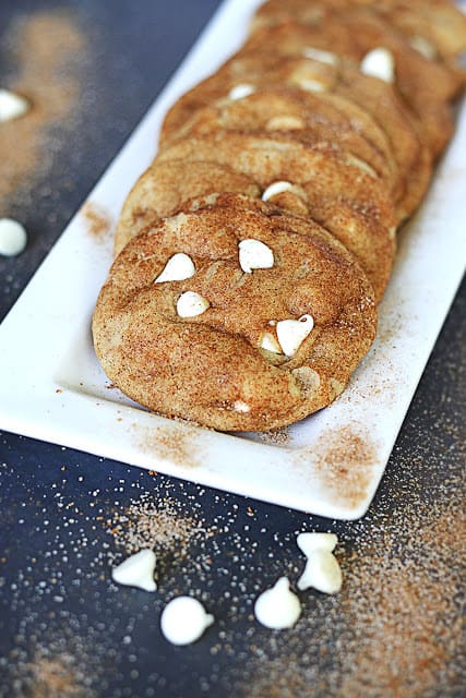 brown butter white chocolate chip snickerdoodles on white tray surrounded by cinnamon and white chocolate chips.