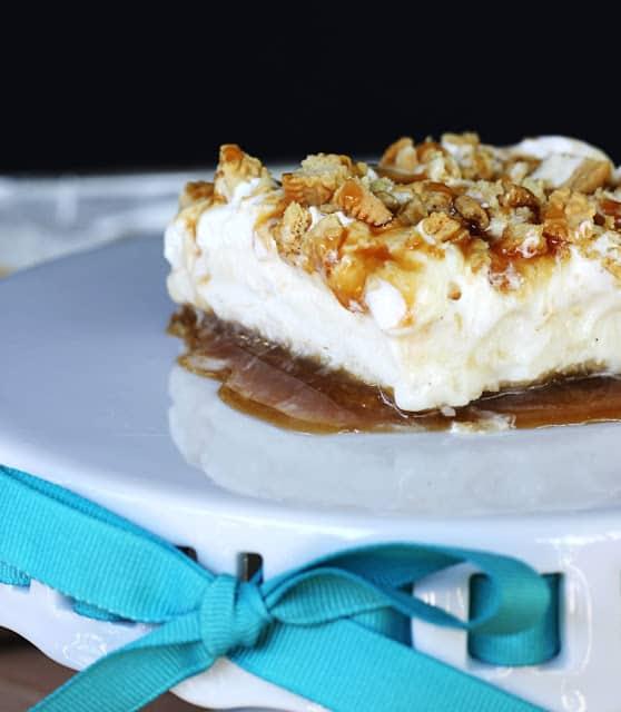 golden Oreo & caramel frozen layer dessert on white glass platter.