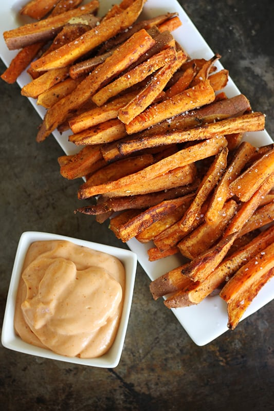 sweet potato fries on white tray with fry sauce in white square bowl.