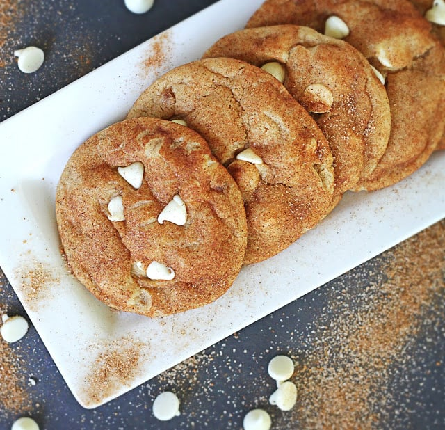top view of brown butter white chocolate chip snickerdoodles on white tray surrounded by cinnamon and white chocolate chips.