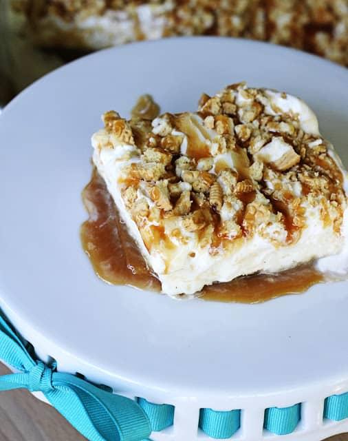 top view of golden Oreo & caramel frozen layer dessert on white glass platter.