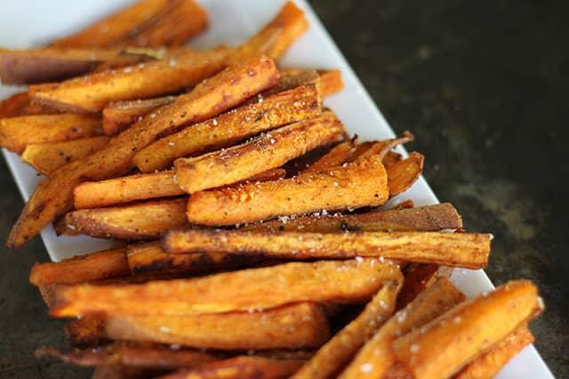 close up of sweet potato fries on white tray.