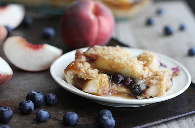 blueberry peach cobbler crisp on small white plate surrounded by blueberries and peaches.