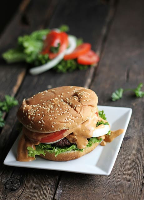 burger on small white square plate with lettuce and tomatoes faded in the background.