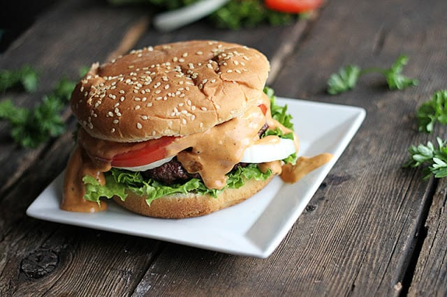 burger on small white square plate.