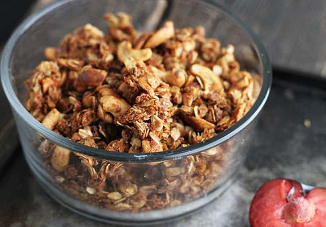 granola in glass bowl on a baking sheet.