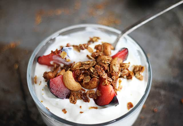 yogurt topped with granola in glass cup with spoon.