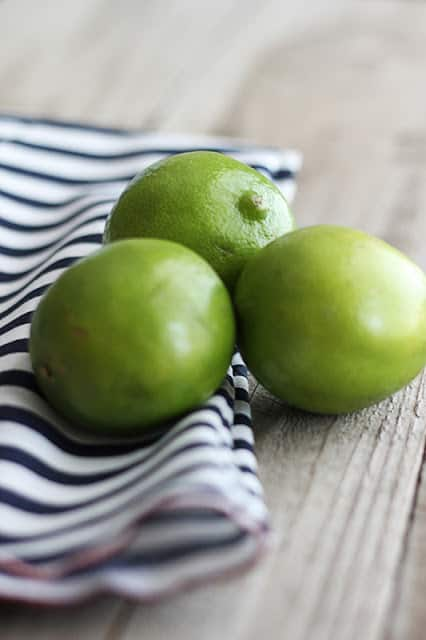 three whole limes on black and white stripped napkin.