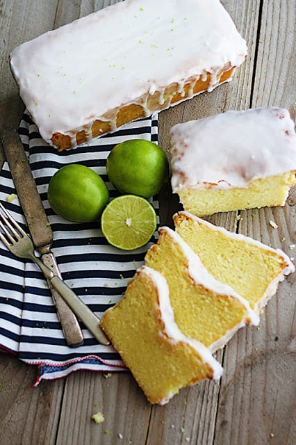 a whole coconut lime {Greek yogurt} pound cake next to one cut up in slices on top of a black and white striped napkin with limes and a fork and knife.