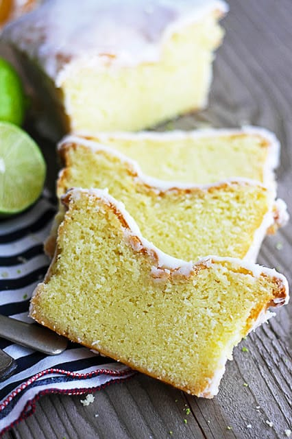 coconut lime {Greek yogurt} pound cake cut in slices with black and white napkin and limes off to the side.