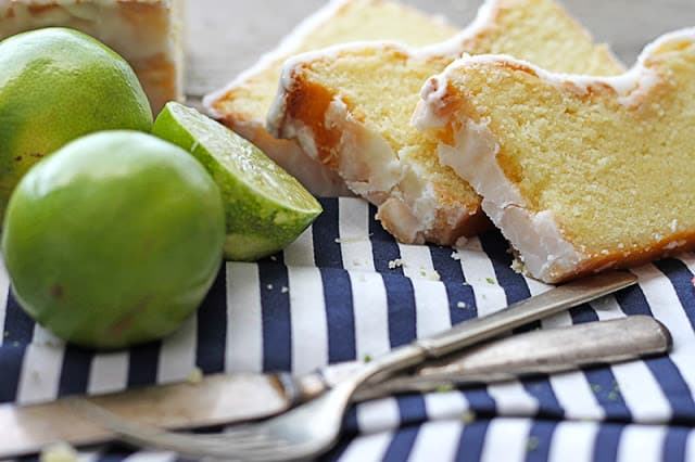 coconut lime {Greek yogurt} pound cake cut in slices with limes and fork and knife on striped napkin.