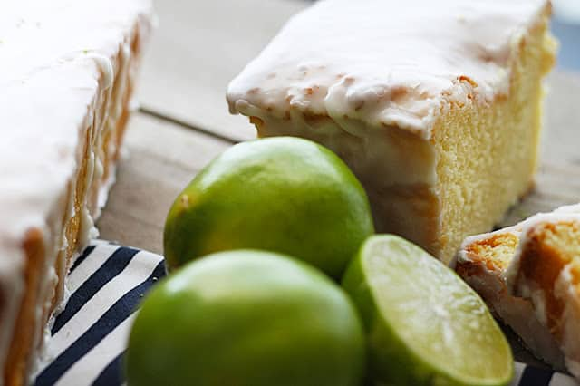 coconut lime {Greek yogurt} pound cake with limes on striped napkin.