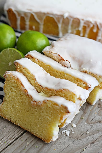 coconut lime {Greek yogurt} pound cake cut in slices with limes, striped napkin and a whole pound cake in the background.