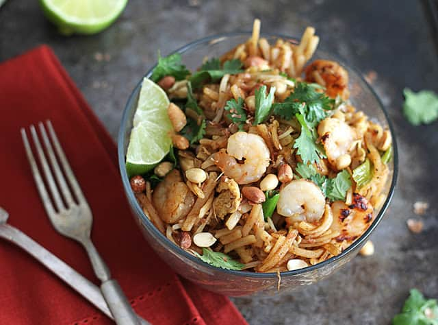shrimp pad Thai in glass bowl with a fork on a red napkin.