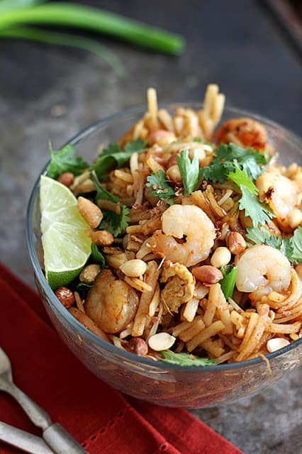 shrimp pad Thai in glass bowl with red napkin and fork.