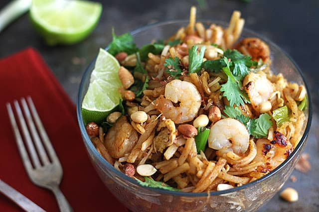 shrimp pad Thai in glass bowl with red napkin, fork and a lime.