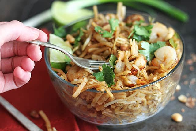 a hand taking some of the shrimp pad Thai from the glass bowl with a fork.
