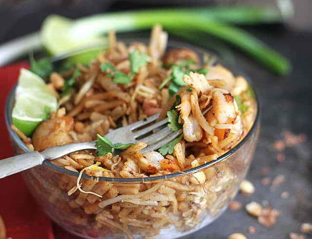 shrimp pad Thai and a fork in a glass bowl.