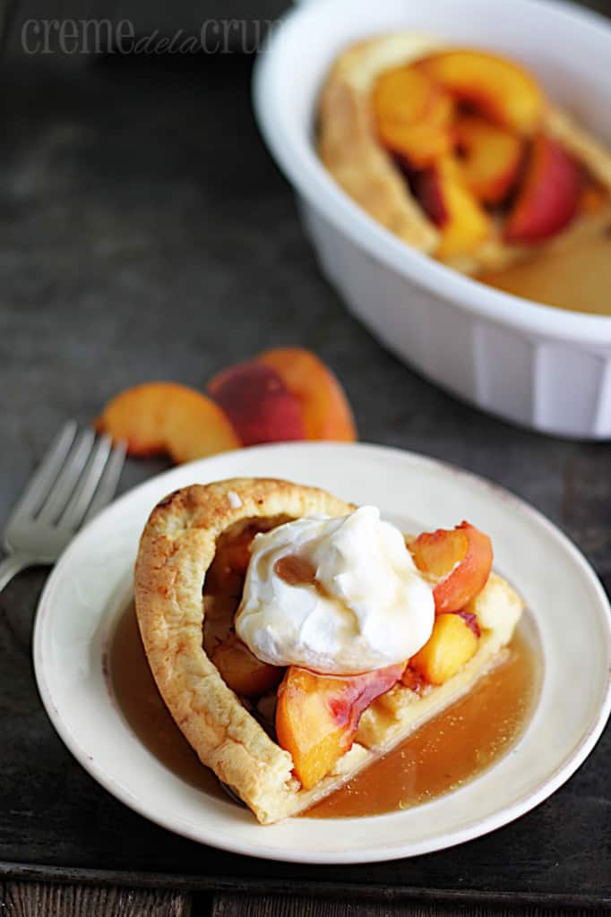 puff pancake on a plate topped with syrup and whipped cream on a baking sheet with a fork, slices of peaches and the rest of the puff pancake in serving bowl.