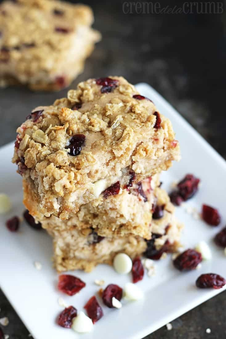 stacked breakfast bars on a plate with Craisins and white chocolate chips.