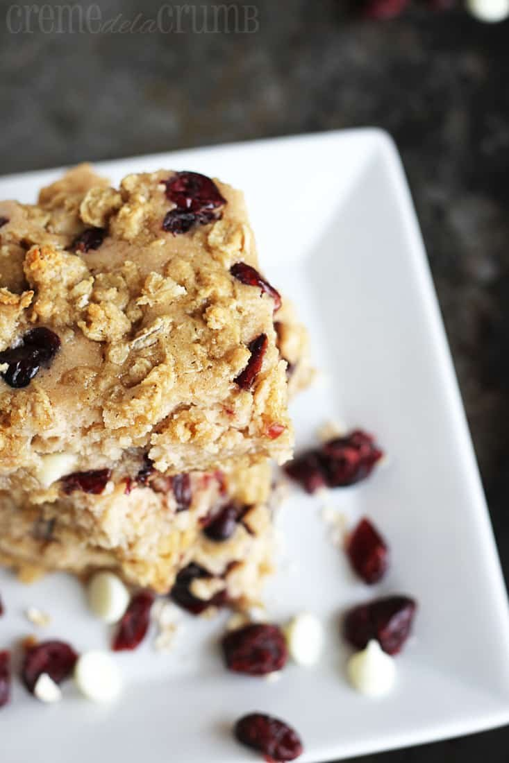 top view of stacked breakfast bars on a plate with Craisins and white chocolate chips.