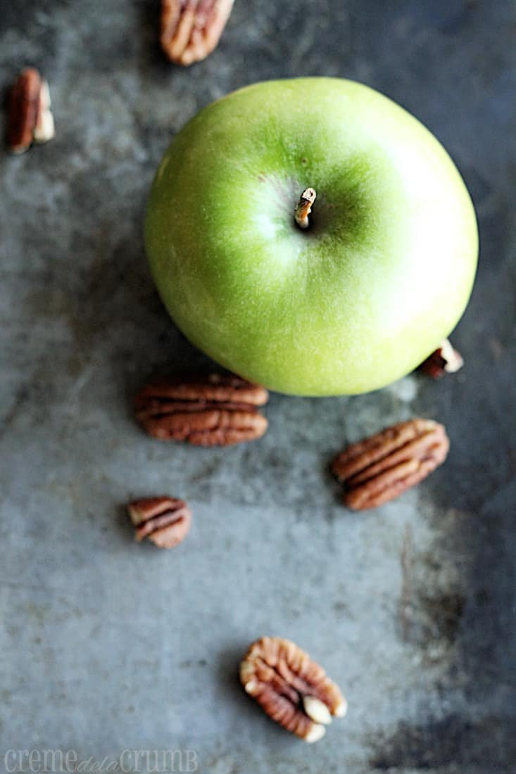 top view of a green apple and pecans.