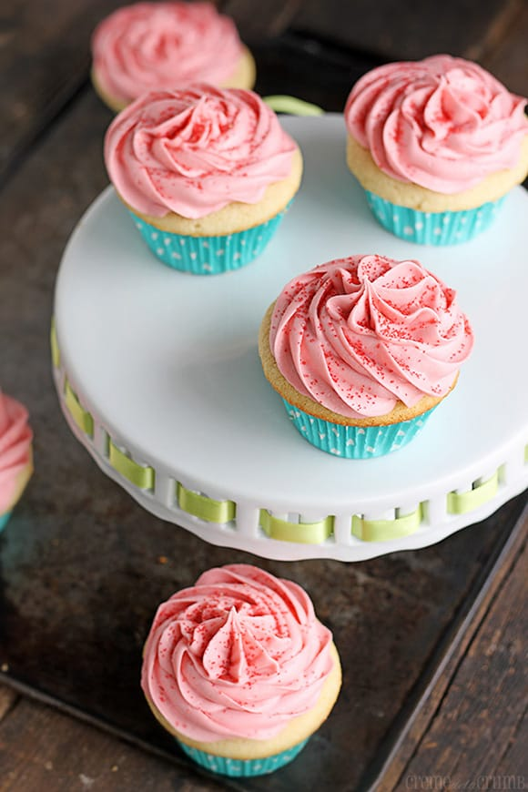 sugar cookie cupcakes on a cake platter on a baking sheet with more sugar cookie cupcakes.