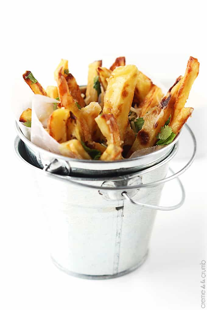garlic parmesan oven fries in a small metal bucket.