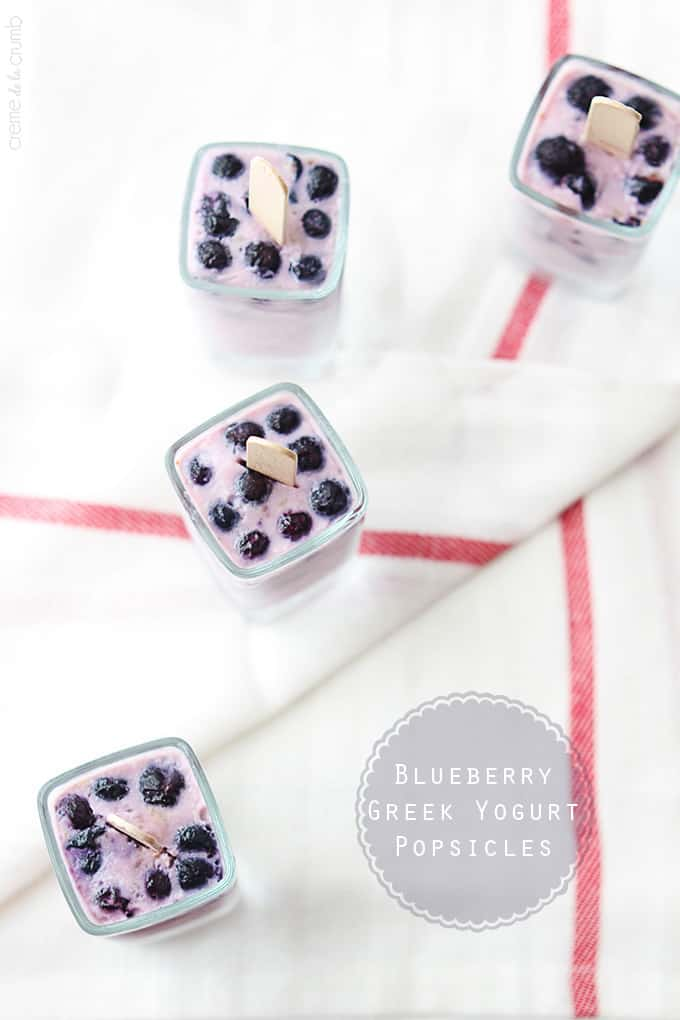top view of blueberry Greek yogurt popsicles upside in glasses with the title of the recipe written on the bottom right corner of the image.