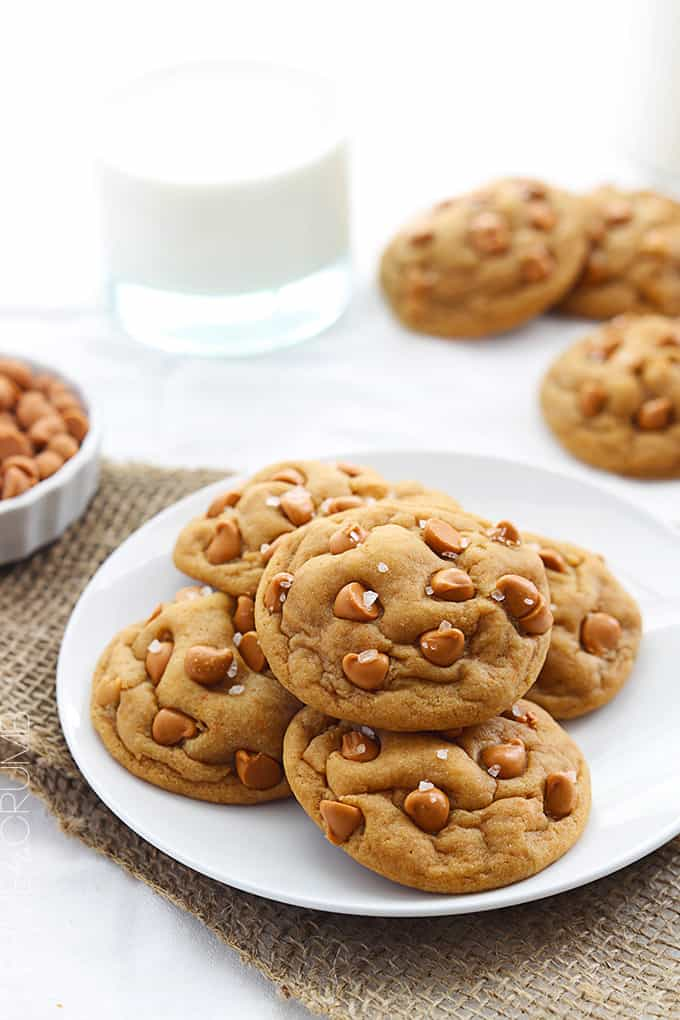 butterscotch chip pudding cookies on a plate with more cookies, butterscotch chips and a glass of milk on the side.