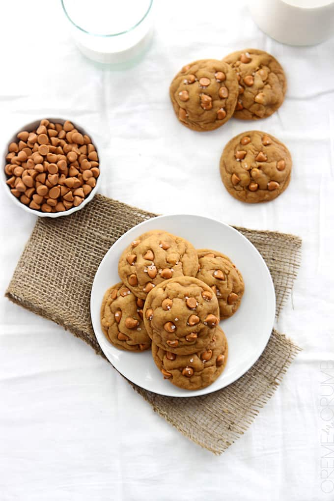 top view of butterscotch chip pudding cookies on a plate with more cookies, butterscotch chips, and milk on the side.