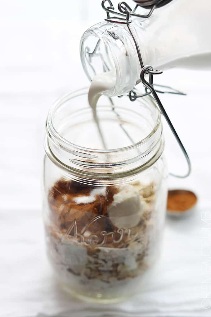 unmixed cinnamon roll overnight oats ingredients in a mason jar with milk being pour inside.