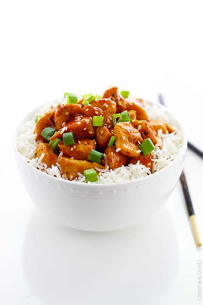 orange chicken on rice in a bowl with chopsticks on the side.