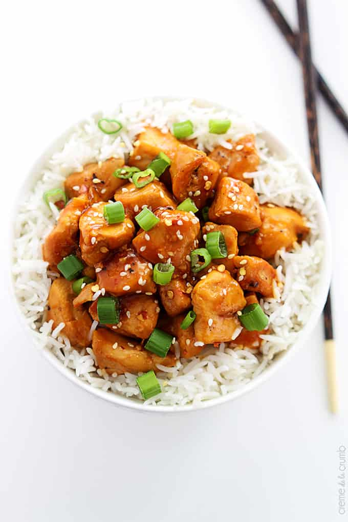 top view of orange chicken on rice in a bowl with chopsticks on the side.