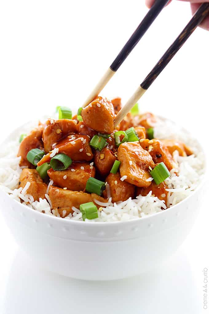 a hand holding chopsticks taking a piece of orange chicken from a bowl of chicken on rice.