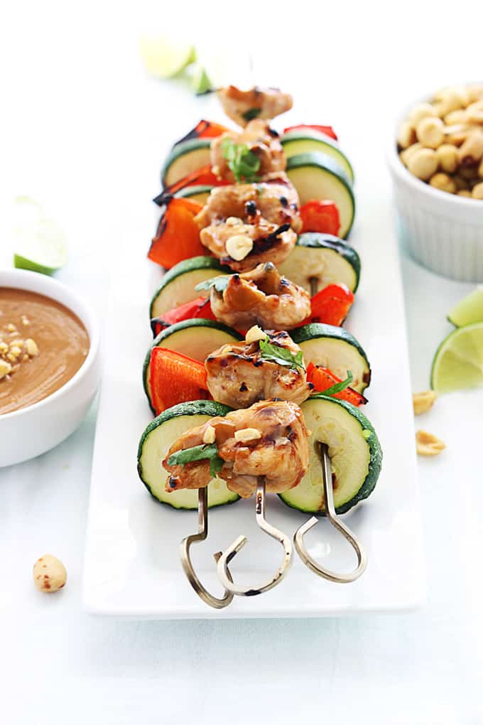 Thai peanut chicken kabobs on a plate with peanut sauce, peanuts, and slices of lime on the side.
