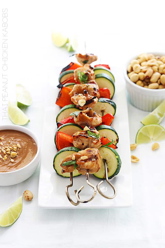 Thai peanut chicken kabobs on a plate with peanut sauce, peanuts, and slices of limes on the side.