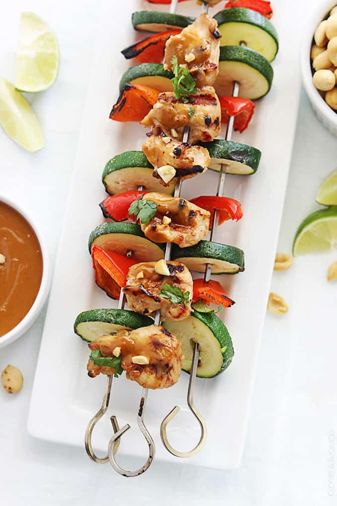 top view of Thai peanut chicken kabobs on a plate with peanut sauce, peanuts, and slices of limes on the side.