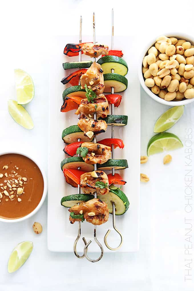 top view of Thai peanut chicken kabobs on a plate with peanut sauce, slices of limes, and peanuts on the side with the title of the recipe written vertically on the bottom right corner going up.