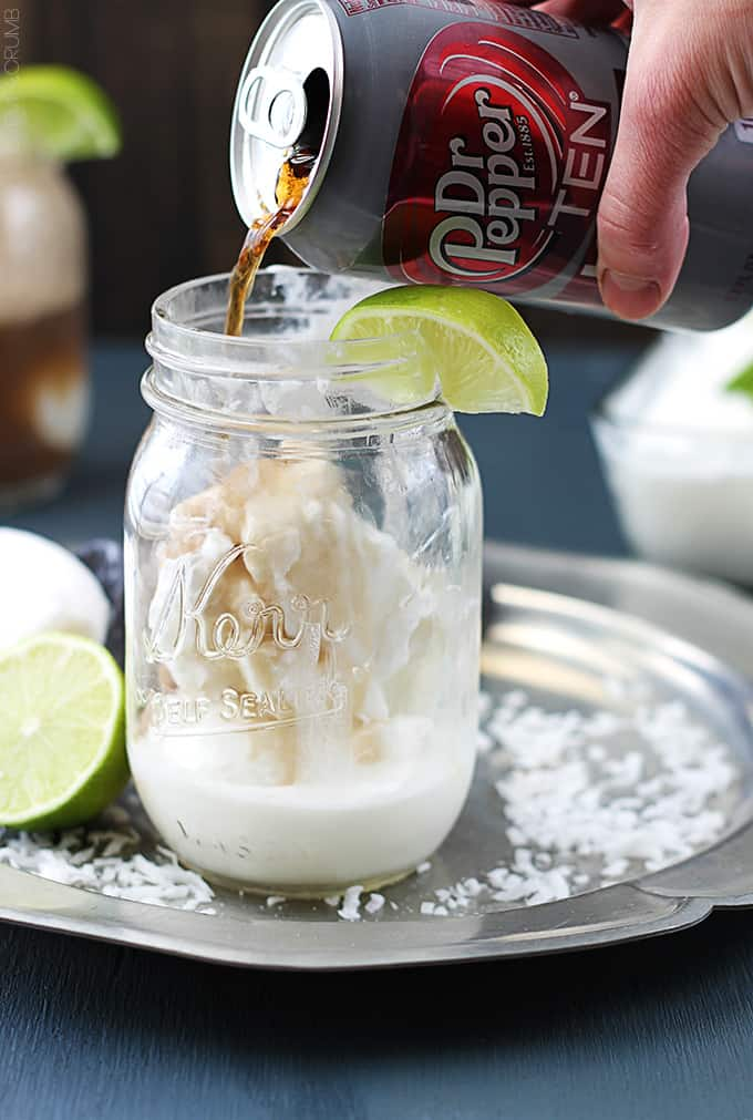 a hand pouring a can of Dr. Pepper into a mason jar with vanilla ice cream in it and a slice of a lime on top.