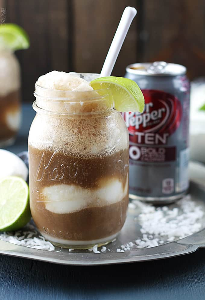 a dirty Dr. Pepper float in a mason jar with a spoon and a slice of a lime on the top with a can of Dr. Pepper in the background.