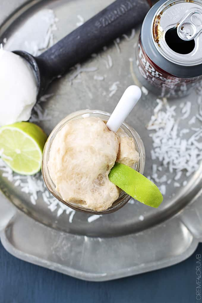 top view of a metal serving tray holding a mason jar of a dirty Dr. Pepper float, a can of Dr. Pepper, half of a lime, and an ice cream scooper with vanilla ice cream on it all surrounded with coconut shavings.