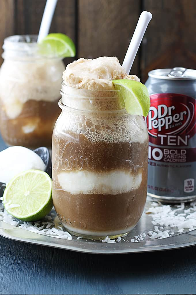 dirty Dr. Pepper floats, a can of Dr Pepper, half of a lime, a scoop of vanilla ice cream on an ice cream scooper, surrounded in coconut shavings on a metal serving tray.