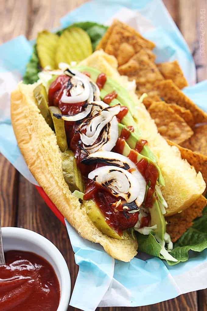 bbq hot dog with avocado & grilled onions with a side of chips on a lunch tray.