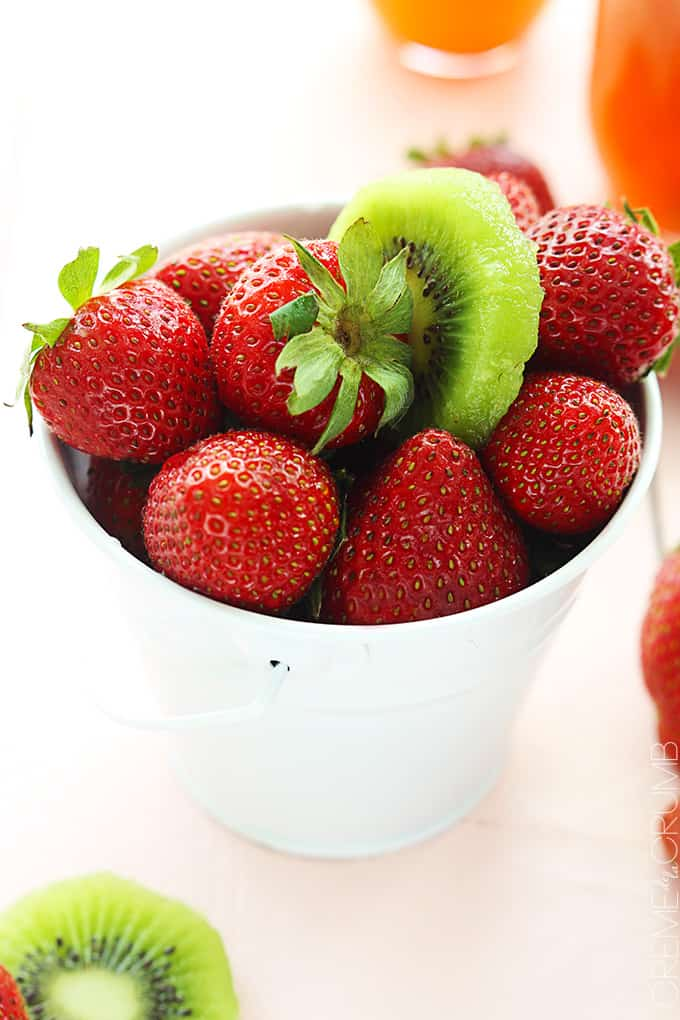 a white metal tin full of strawberries with a slice of a kiwi on top.