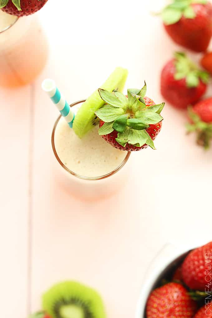 top view of strawberry kiwi lemonade in a glass with a slice of kiwi and a whole strawberry on the top of the glass with a straw.
