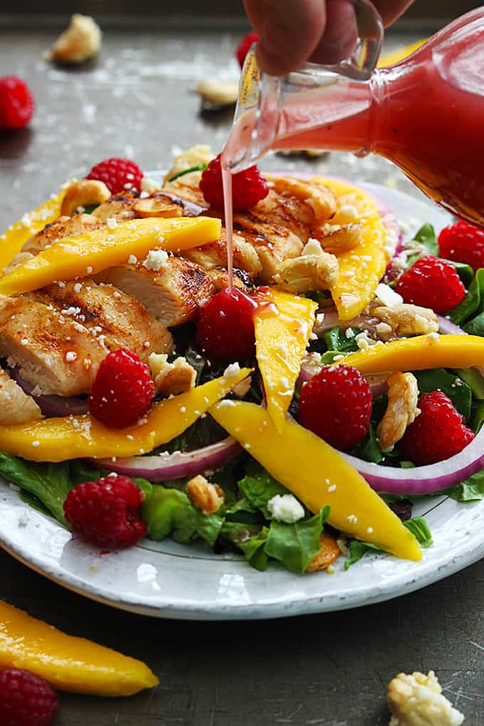 a hand pouring raspberry vinaigrette on raspberry mango chicken cashew salad on a plate surrounded by more fruit.