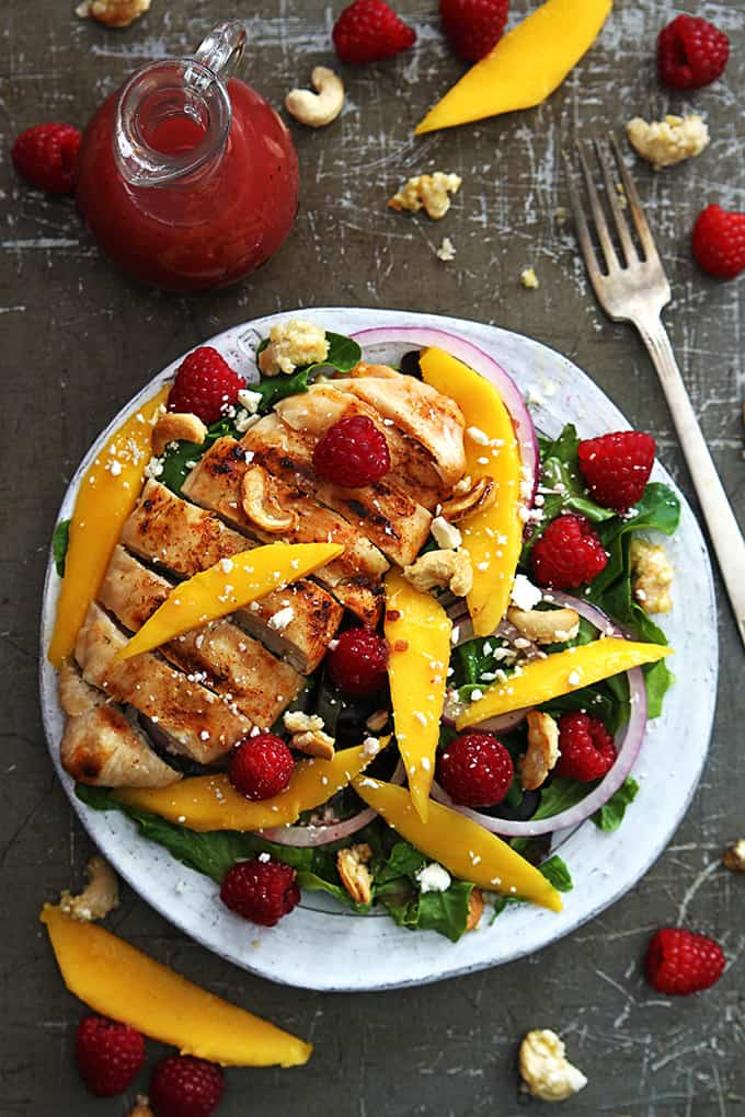 top view of raspberry mango chicken cashew salad on a plate with a fork, raspberry vinaigrette, cashews and more fruit on the side.