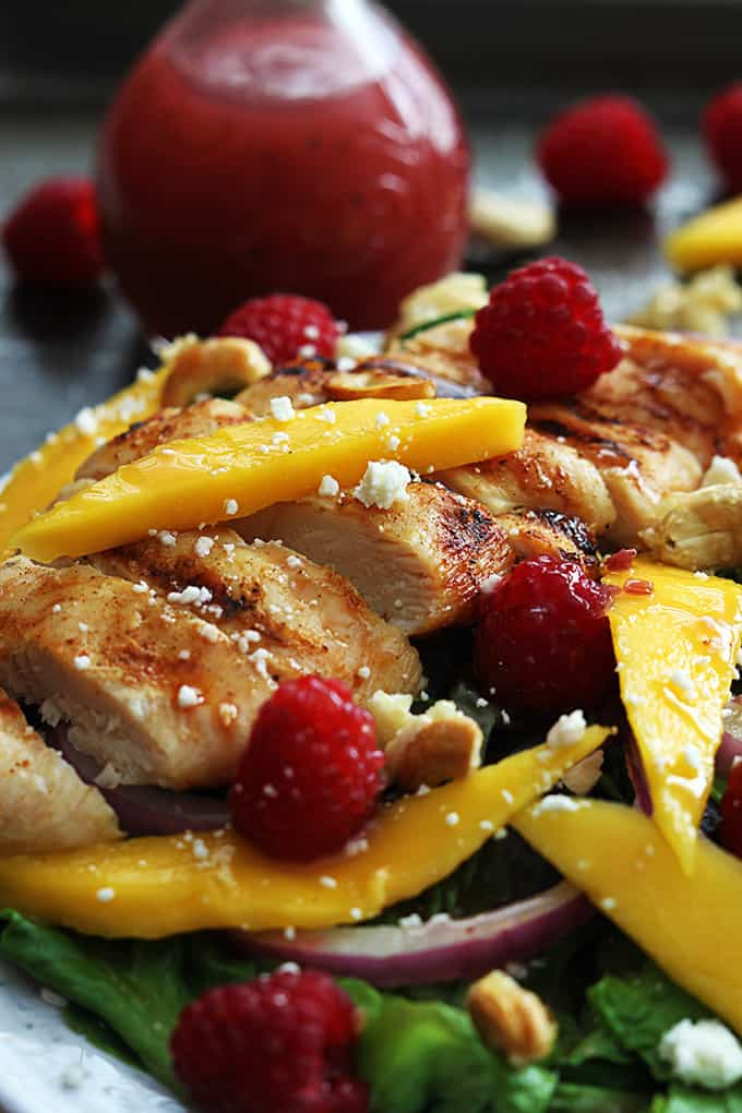 close up of raspberry mango chicken cashew salad on a plate with more fruit faded in the background.